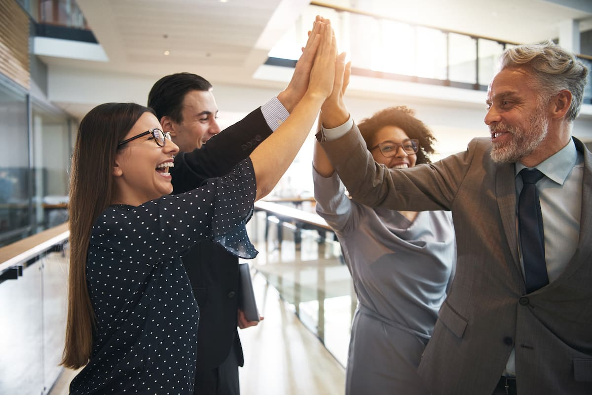business-team-high-fiving-each-other-in-an-office