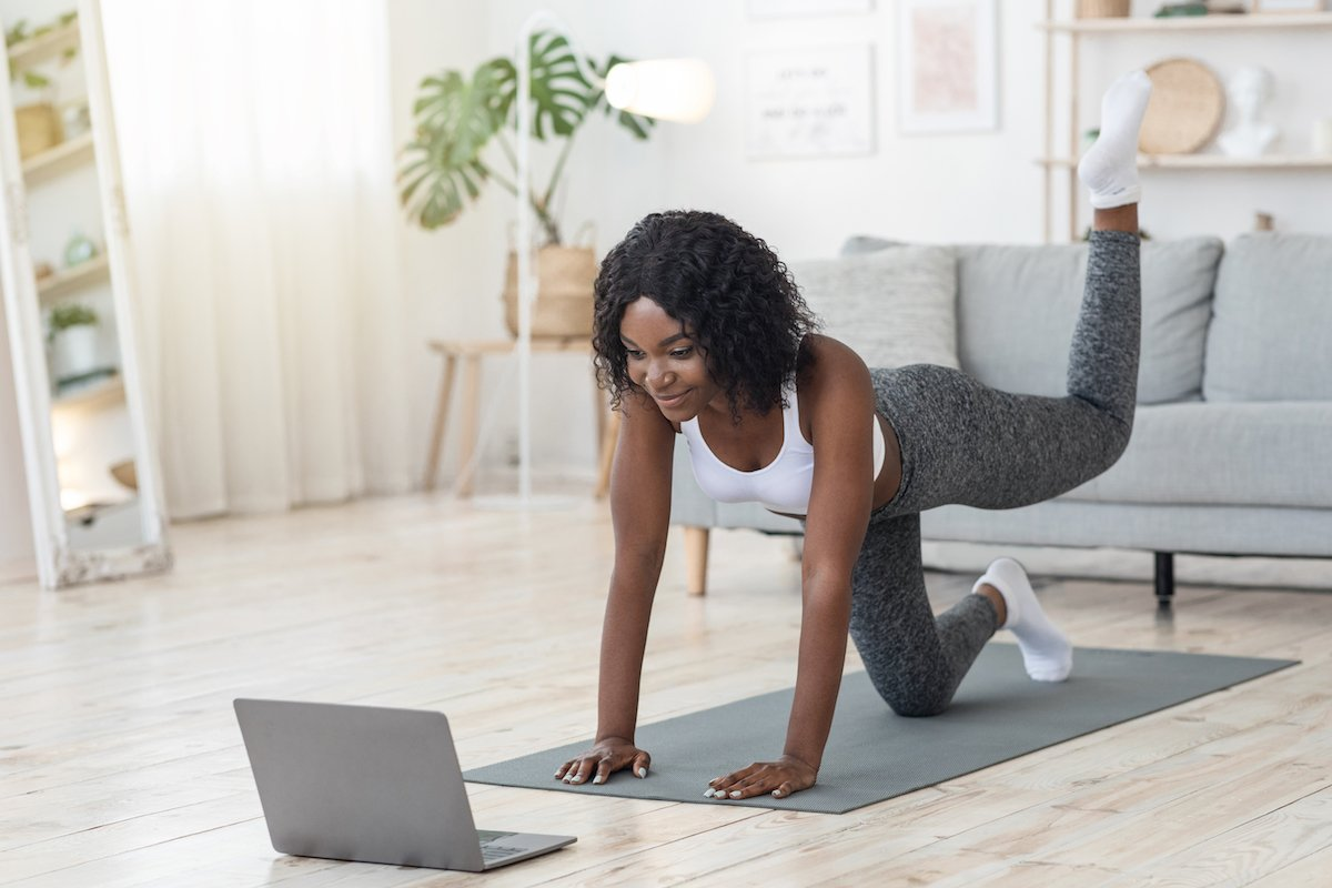 girl-making-workout-at-living-room-in-front-of-lap-4TPAVFZ